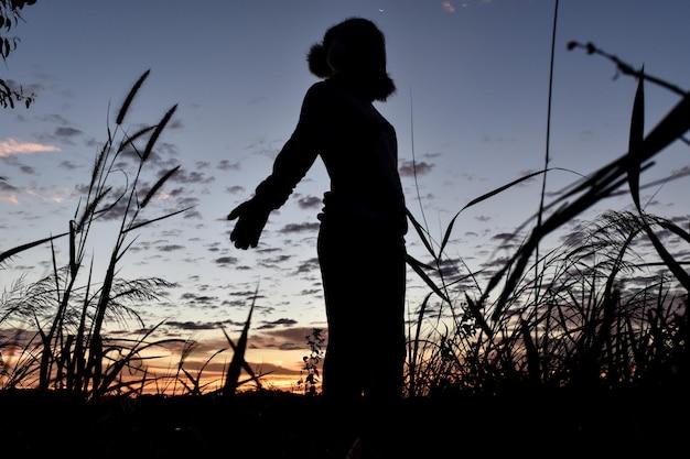 Silhouetvrouw open wapensverblijf onder zonsopgang genietend van het succes, vrijheid.