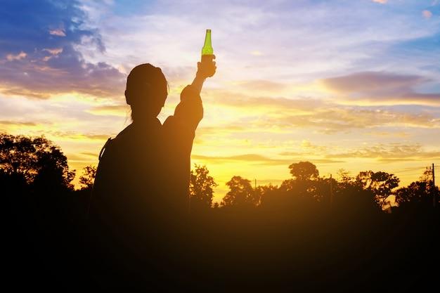 Silhouetvrouw opgeheven handen die een groene bierfles op de zonsonderganghemel houden