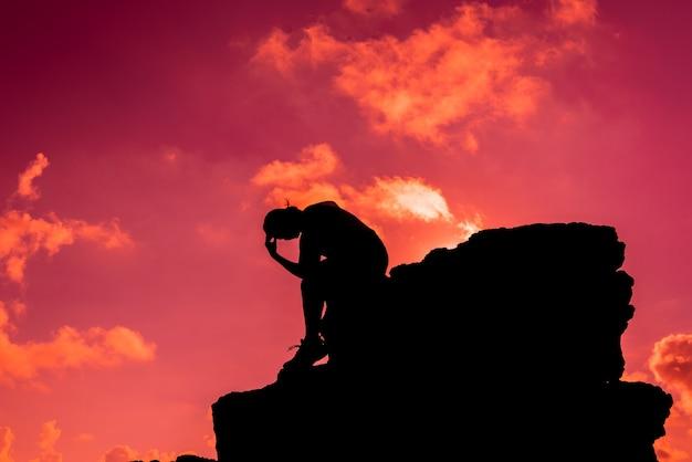 Silhouetvrouwen die alleen op de rots zitten. geestelijke gezondheid, ptss en zelfmoordpreventie.