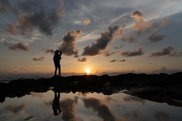 Silhouetvrouwen met mooie bewolkte hemel in zonsondergangtijd en bezinningsvijver / achtergrondtextuur / aardhemel