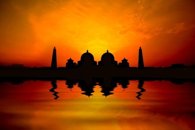 Silhoutte afbeelding van zonsondergang over een moskee met waterreflectie