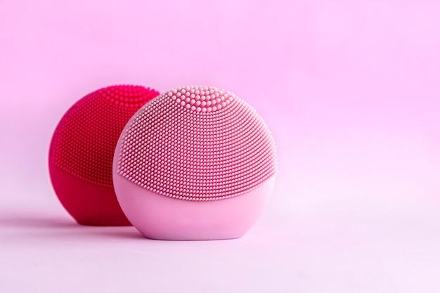 Siliconen gezichtsreinigingsborstels met reinigingsborstel voor het masseren van huidverzorging op roze achtergrond.
