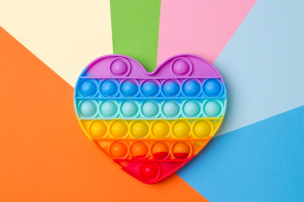 Siliconen regenboog hart speelgoed op kleurrijke veelkleurige achtergrond