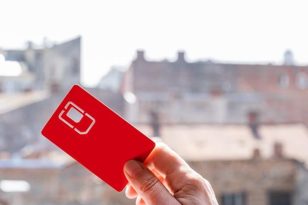 Sim-kaartsleuf richting hemel hand straat rood kopie ruimte 4g 5g