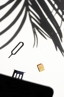 Sim-kaartsleuf witte achtergrond schaduw tropische bladeren palm telefoon kopie ruimte 4g 5g