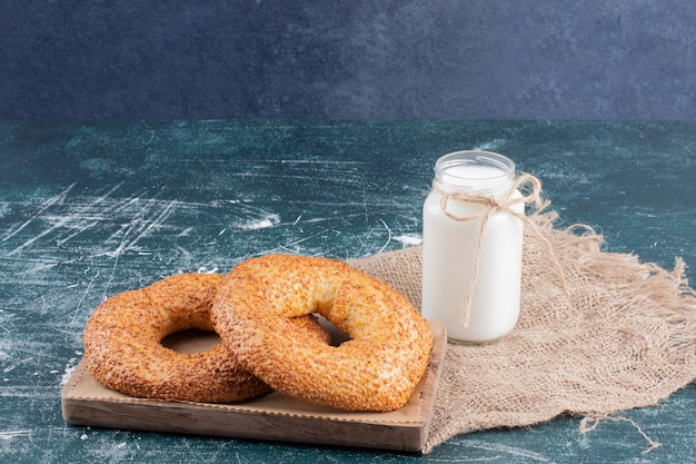 Simit bagels met sesam en kruik melk op blauw.
