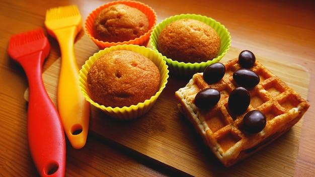 Simpele mini muffins in kleurrijke siliconen bakvormen en wafels. keuken en kookconcept op houten achtergrond