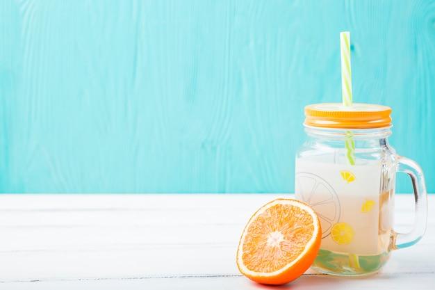 Sinaasappel dichtbij glas met stro en limonade