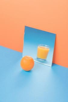 Sinaasappel dichtbij sap in spiegel op blauwe geïsoleerde lijst
