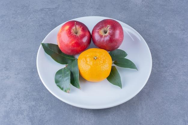 Sinaasappel en appels met bladeren op plaat op marmeren tafel.