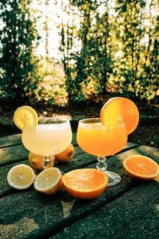 Sinaasappel- en citroensap in glazen beker op rustieke tafel in het park