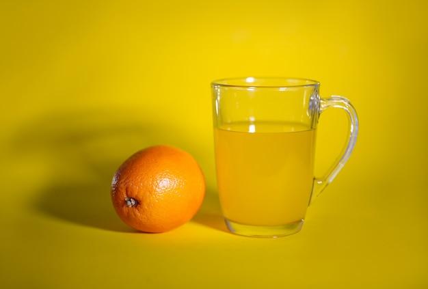 Sinaasappel en een glas sinaasappelsap op geel