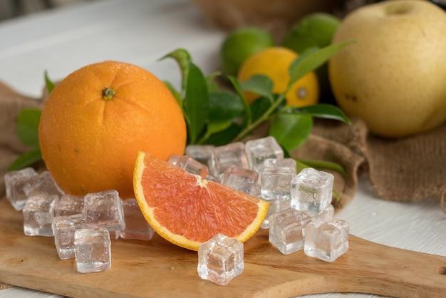 Sinaasappel en gesneden op een houten plaat met ijsblokjes en fruit als achtergrond