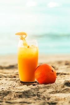 Sinaasappel en glas met sap dat op zandig strand wordt geplaatst
