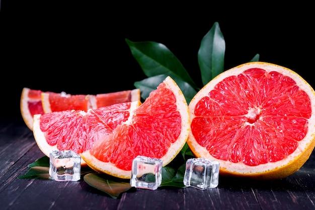 Sinaasappel en grapefruit juice op een houten zwarte achtergrond