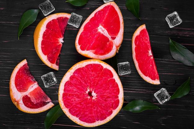 Sinaasappel- en grapefruitsap op een houten zwarte achtergrond