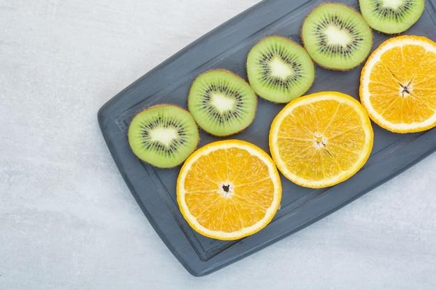 Sinaasappel- en kiwiplakken op donkere plaat. hoge kwaliteit foto