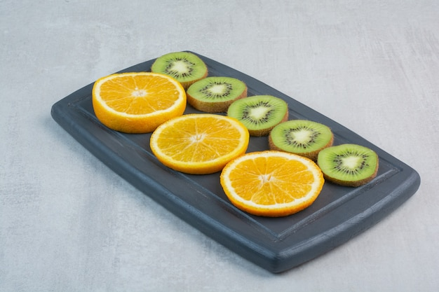 Sinaasappel en kiwiplakken op donkere plaat