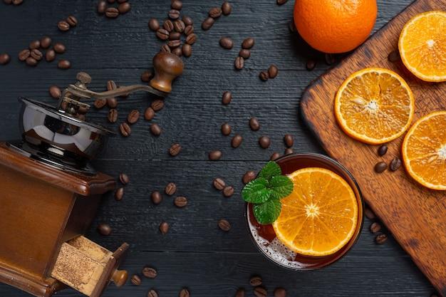 Sinaasappel en koffiecocktail op het donkere oppervlak.