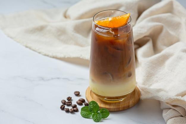 Sinaasappel en koffiecocktail op het witte oppervlak.