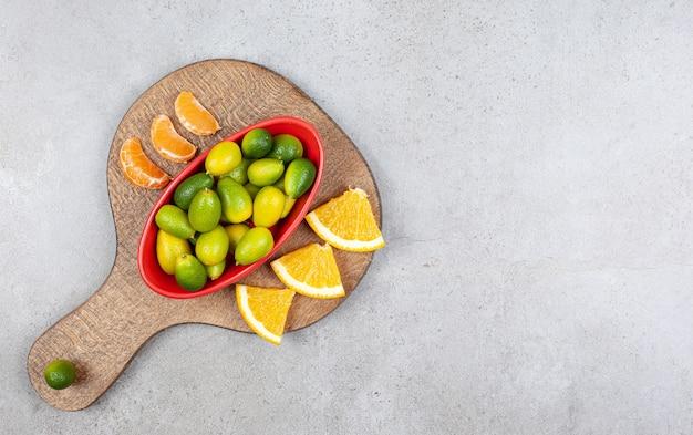 Sinaasappel en mandarijn plakjes whit kom met kumquats op een houten bord.