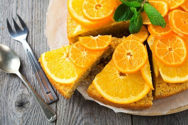Sinaasappel- en mandarijncake met polenta, ondersteboven op de oude houten ondergrond. bovenaanzicht. selectieve aandacht.