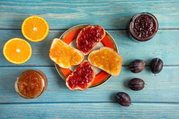 Sinaasappel- en pruimconfituur in een glazen pot en op de toastbroodjes in een bord.