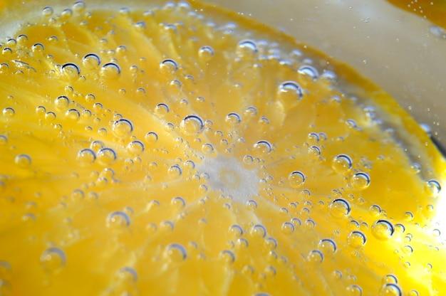 Sinaasappel in bruisend water met bubbels. macro.