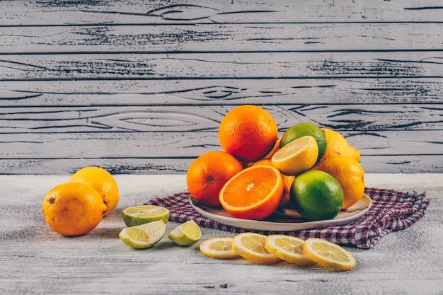 Sinaasappel met groene en gele citroenen met plakken in een plaat en op doek en grijze houten achtergrond, zijaanzicht.