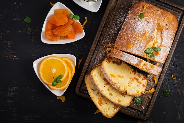 Sinaasappelcake met gedroogde abrikozen en poedersuiker. bovenaanzicht