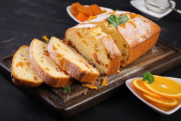 Sinaasappelcake met gedroogde abrikozen en poedersuiker.