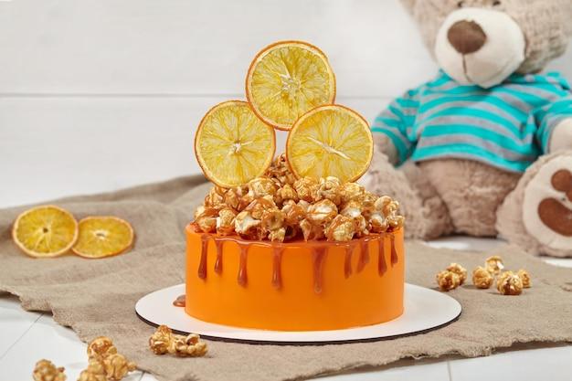 Sinaasappelcake met gekarameliseerde popcorn en gekonfijte citrusschijfjes