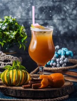 Sinaasappelcocktail met kaneelstokjes en citroen, limoenmix.