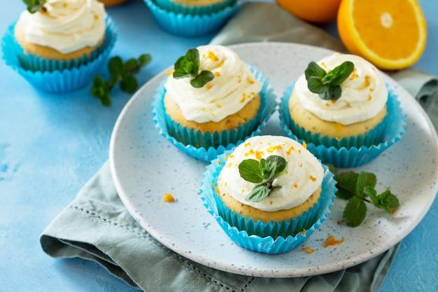 Sinaasappelcupcakes met wrongelroom op de feestelijke kersttafel