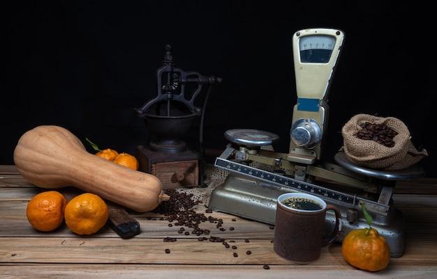 Sinaasappelen, bananen, een pompoen en oude accessoires op hout