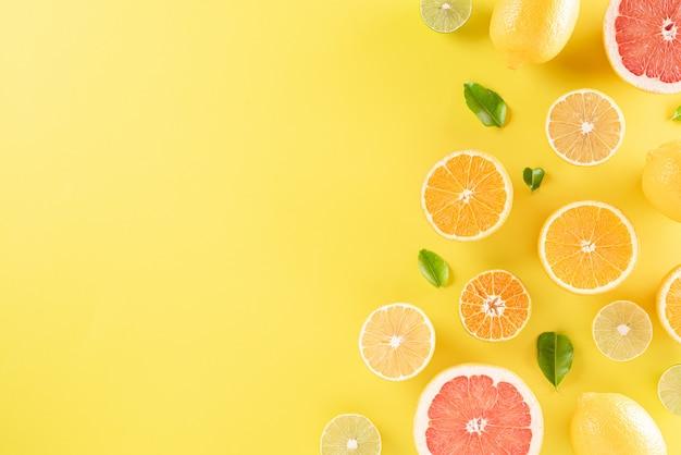 Sinaasappelen, citroen en groene bladeren op pastel geel papier, kopie ruimte.