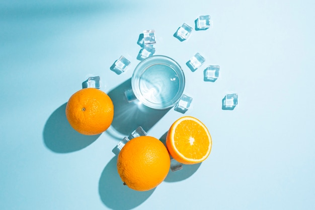Sinaasappelen, een glas water en ijsblokjes op een tafel