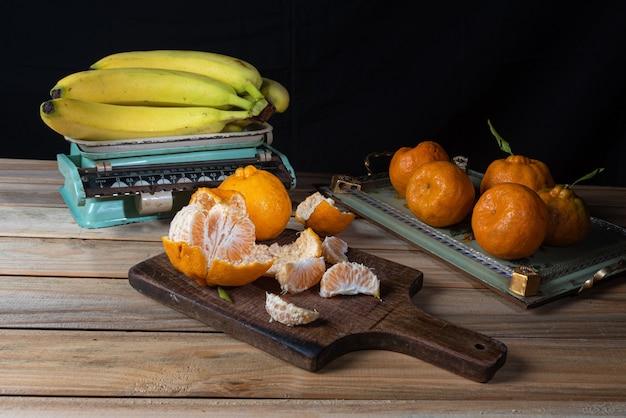 Sinaasappelen en bananen en accessoires op een houten tafel