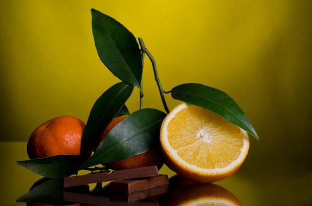 Sinaasappelen en chocolade geïsoleerd op donkergeel