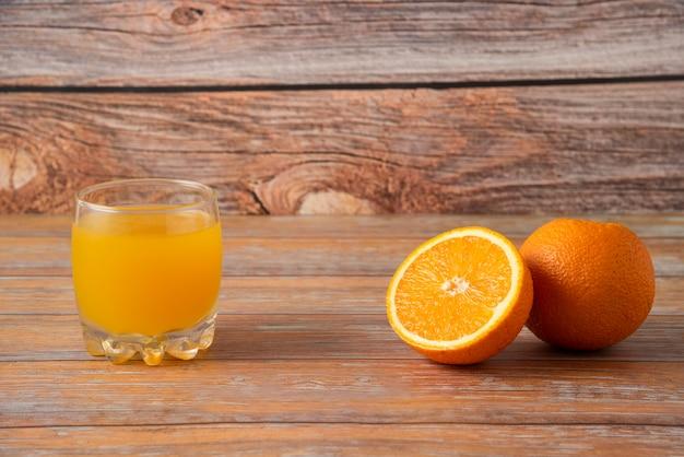 Sinaasappelen en een glas sap dat op houten wordt geïsoleerd
