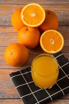 Sinaasappelen en een glas sap op een zwarte theedoek, bovenaanzicht