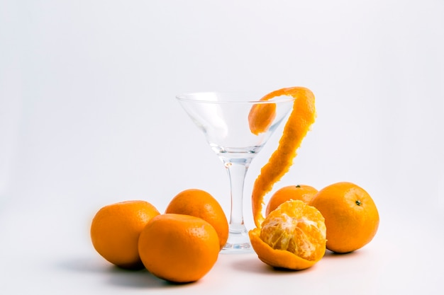 Sinaasappelen en een wijnglas op een witte lijst.