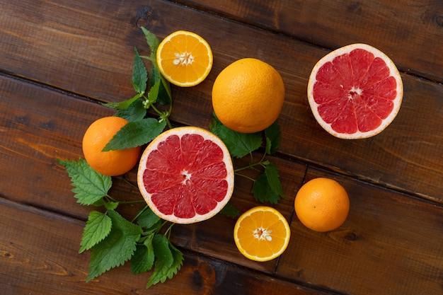 Sinaasappelen en grapefruit op een bruine houten achtergrond