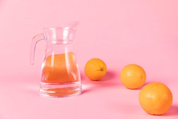 Sinaasappelen en kruik water op roze achtergrond