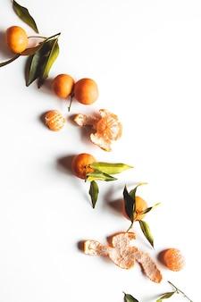 Sinaasappelen fruit samenstelling met groene bladeren en plak op witte houten achtergrond, bovenaanzicht