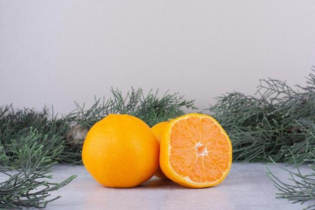 Sinaasappelen gebundeld naast pijnboomtakken op wit oppervlak