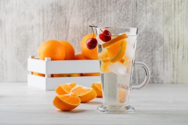 Sinaasappelen in een houten doos met fruit gegoten water zijaanzicht over witte oppervlakte