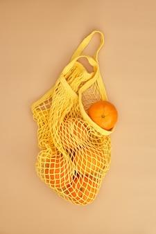 Sinaasappelen in een koordzak op beige ondergrond