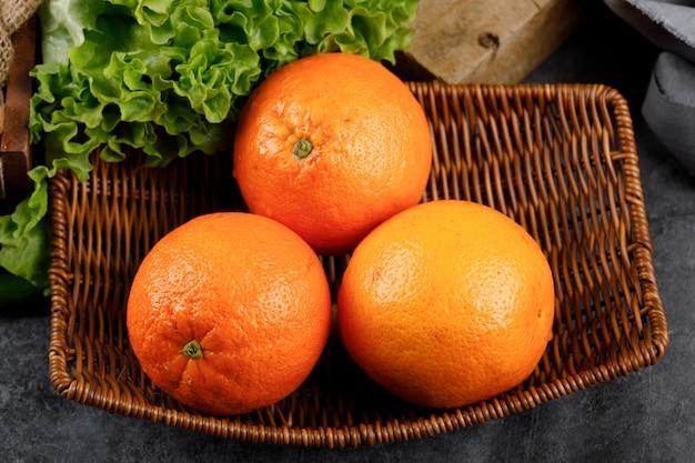 Sinaasappelen in een rustieke mandschotel.