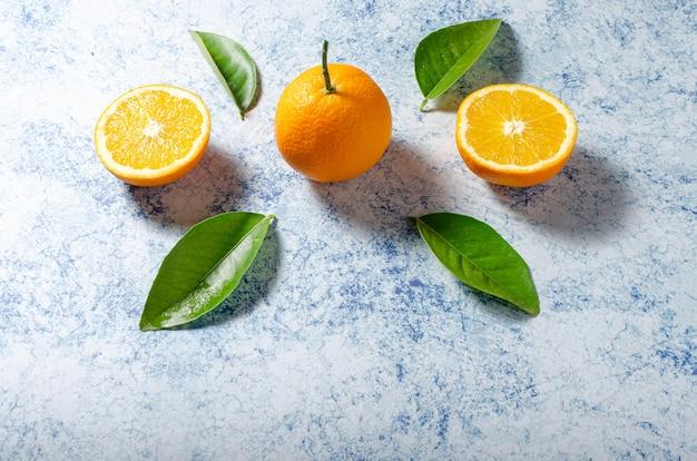 Sinaasappelen met hun bladeren op een blauwe achtergrond